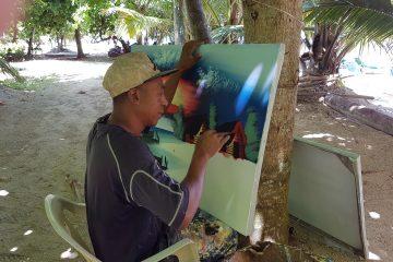 Pintando entre playas se gana la vida, bajo la sombra de un almendro